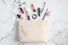 Makeup Bag With Cosmetic Products Spilling Out On To Marble Table. Stylish Make Up Artist Pouch With Beauty Products. Flat Lay, Top View