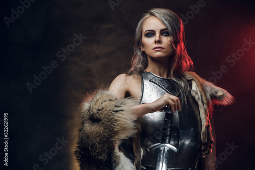 Foto Portrait of a beautiful warrior woman holding a sword wearing steel cuirass and fur