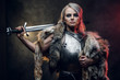 canvas print picture - Portrait of a beautiful warrior woman holding a sword wearing steel cuirass and fur. Fantasy fashion. Studio photography on a dark background. Cosplayer as Ciri from The Witcher.