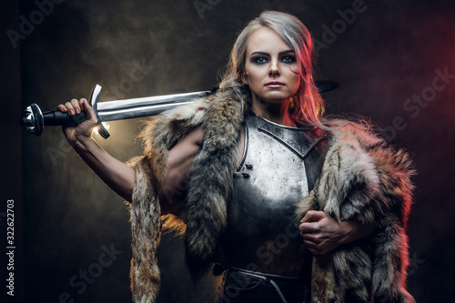 Obraz na plátně Portrait of a beautiful warrior woman holding a sword wearing steel cuirass and fur