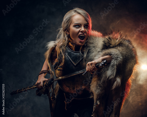 Photo Fantasy woman knight wearing cuirass and fur, holding a sword and rushes into battle with a furious cry
