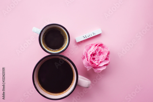 Fototapeta Two cups of coffee, a delicate flower and numbers. Greeting card for Women's Day March 8th. Trendy pink background. March 8 and the concept of