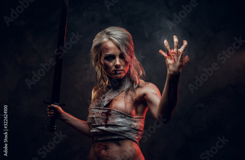 Fototapeta Naked Fantasy woman warrior wearing rag cloth stained with blood and mud in the heat of battle