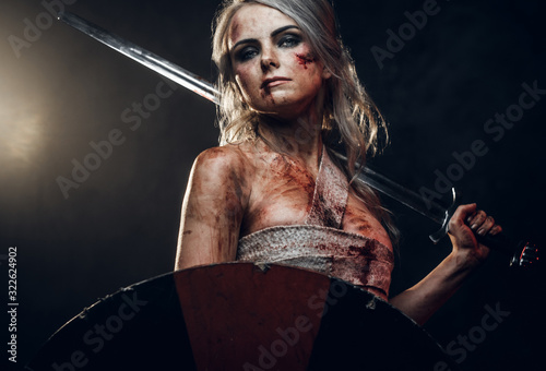 Fantasy woman warrior wearing rag cloth stained with blood and mud, holding sword and shield Wallpaper Mural