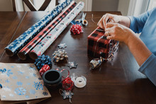 Hands Wrapping Present With Gift Wrapping Supplies On Table.