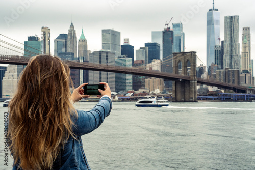 attractive woman using her smartphone with the New York skyline in the background - 322630593