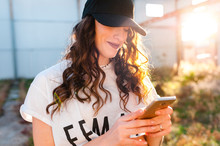 Cheerful Millennial Woman Using Smartphone In Street At Sunset
