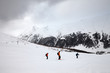 Leinwanddruck Bild Off-piste snowy ski slope with skiers in high mountains and cloudy sky