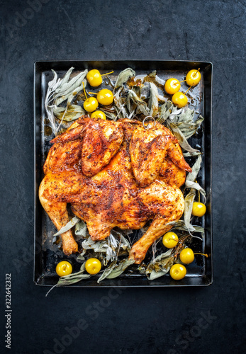 Barbecue spatchcocked chicken al mattone chili with mini apples and sage leaves as top view on an old metal tray