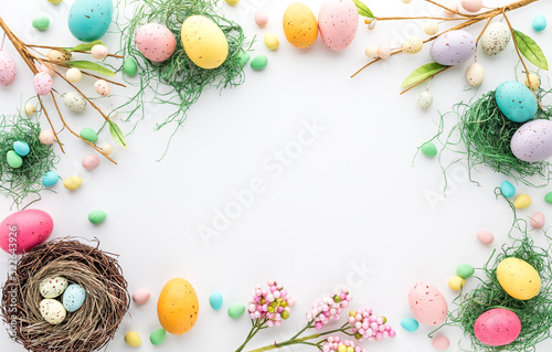 Photo Top down view of an Easter border frame of robin's eggs and chocolate eggs with