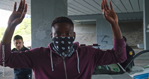 Stampa su Tela Close-up black man perpetrator wearing mask raising his hands by police order