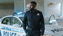 Attractive African American Young Man Cops Stand Near Patrol Car Look At Camera Enforcement Happy Officer Police Uniform Auto Safety Security Communication Control Policeman Close Up Slow Motion