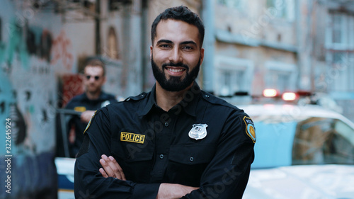 Foto Smiling young man cops stand near patrol car look at camera enforcement happy of