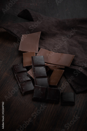 Photo pieces of bitter and milk chocolate on a dark wooden surface