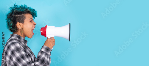 Fotografía african american girl or woman with megaphone isolated on blue background