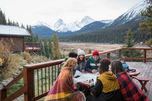 Friends Looking At Map On Cabin Balcony With Mountain View, Rocky Mountains, Canada