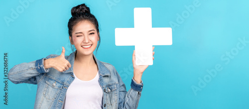 Fotomural Banner of asian woman smiling, showing plus or add sign and thumb up on blue background