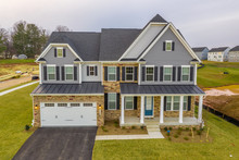 View Of Custom Built Luxury Colonial Style Estate Home With Two Car Garage Covered Porch, Large Windows, Complex Roof In A New American Neighborhood Street