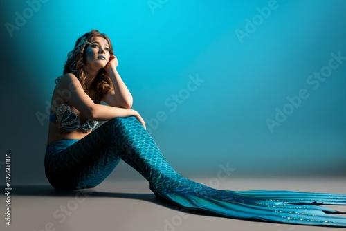 Woman in mermaid image sitting on the floor shot