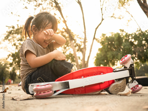 Cute Asian little girl sitting on the ground after falling off her scooter at summer park Canvas Print