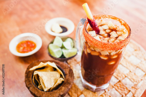 Fototapeta Michelada beer with Tomato Juice, lemon and candy in jar, Mexican drink in summe
