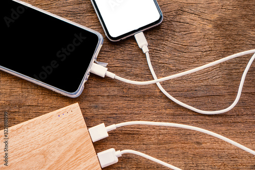 Leinwand Poster two smart phone charging with power bank on wooden table