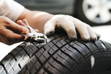 Mechanic Repair A Tire Puncture From A Nail Or Screw. Car Repair And Maintenance Concept
