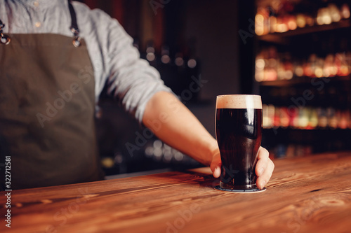 Photo Barman hold dark cold fresh beer to client in pub behind bar
