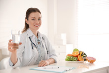 Nutritionist With Glass Of Water At Desk In Office. Space For Text