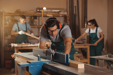 Professional Carpenter Working With Surface Planer And Colleagues In Workshop