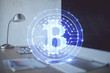 Multi exposure of blockchain and crypto economy theme hologram and table with computer background. Concept of bitcoin cryptocurrency.