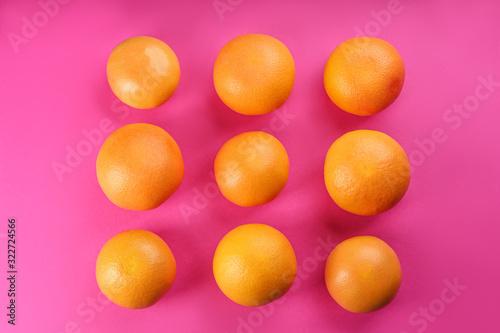 Fotografie, Obraz Tasty ripe grapefruits on magenta background, flat lay