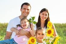 Cheerful Family With Sunflowers In Field