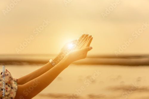 Young woman praying Hands  at sunset Fototapeta
