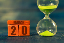 March 20th. Day 20 Of Month,Handmade Wood Cube With Date Month And Day And Hourglass With Green Sand. Time Passing Away. Artistic Coloring.  Spring Month, Day Of The Year Concept