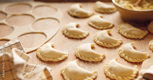 Photo Raw dumplings with cheese and potato filling prepared for cooking on a wooden board, close-up view