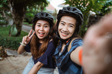 Two Young Woman Wearing Helmet...
