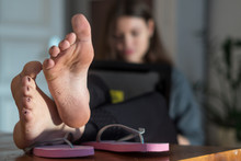 Woman With Feet On The Table Working On The Computer