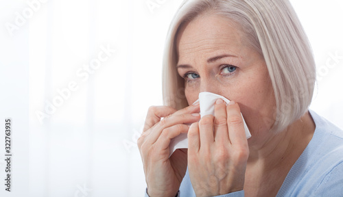 Healthcare, cold, allergy and people concept, sick woman blowing her runny nose Canvas Print
