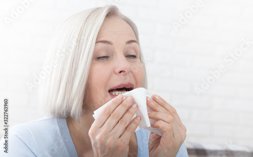 Obraz na plátne Healthcare, cold, allergy and people concept, sick woman blowing her runny nose