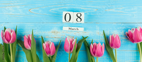 Obraz na plátně Pink tulip flower and 8th March calendar on blue wood table background with copy space for text
