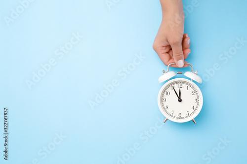 Cuadros en Lienzo Woman hand holding white alarm clock on light blue table background