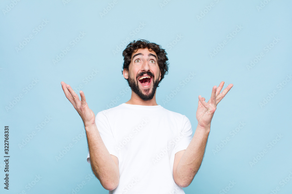 Fototapeta young crazy bearded man feeling happy, amazed, lucky and surprised, celebrating victory with both hands up in the air against flat wall