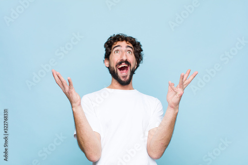 young crazy bearded man feeling happy, amazed, lucky and surprised, celebrating Wallpaper Mural