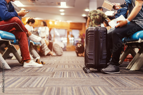 Obraz people sitting and waiting for check in at airport. A man and luggage at the airport terminal. - fototapety do salonu