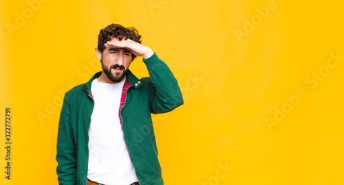 Photo young crazy bearded man looking bewildered and astonished, with hand over forehe