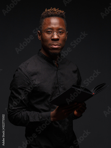 Fototapeta A young African man in black clothes on a dark background holds in the hands of a book. obraz na płótnie