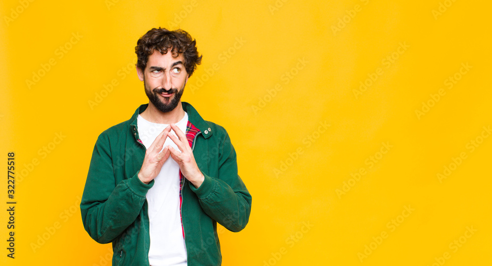 Fototapeta young crazy bearded man scheming and conspiring, thinking devious tricks and cheats, cunning and betraying against flat wall