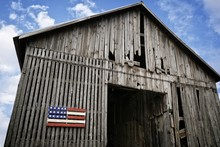 Low Angle Shot Of An Old Wooden Barn With A Painted Wood American Flag