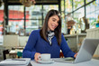 Side view of attractive caucasian brunette in blue sweater sitting in cafe, holding cup of coffee and using laptop for writing e-mail. Remote business concept.